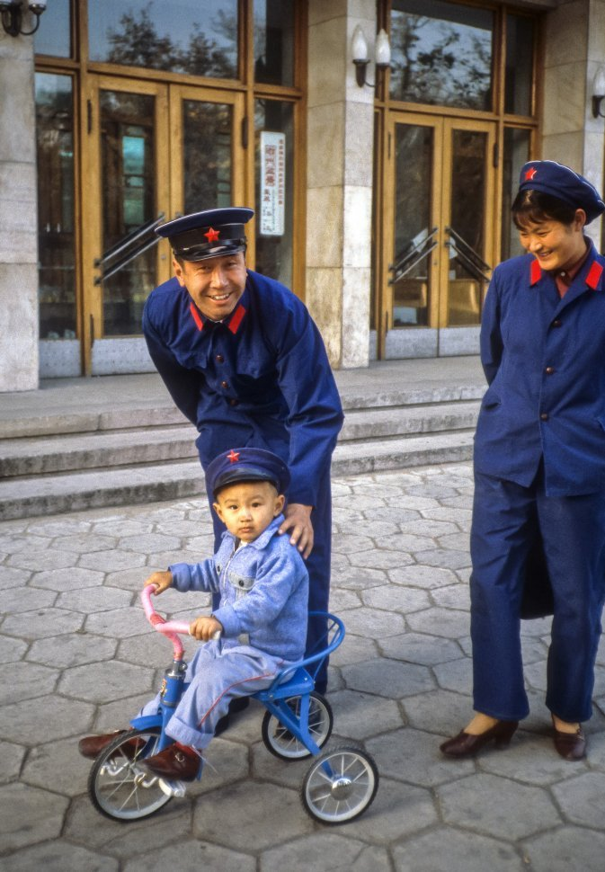 Free image of Couple in uniform pushing a small child on a tricycle, China, Asia