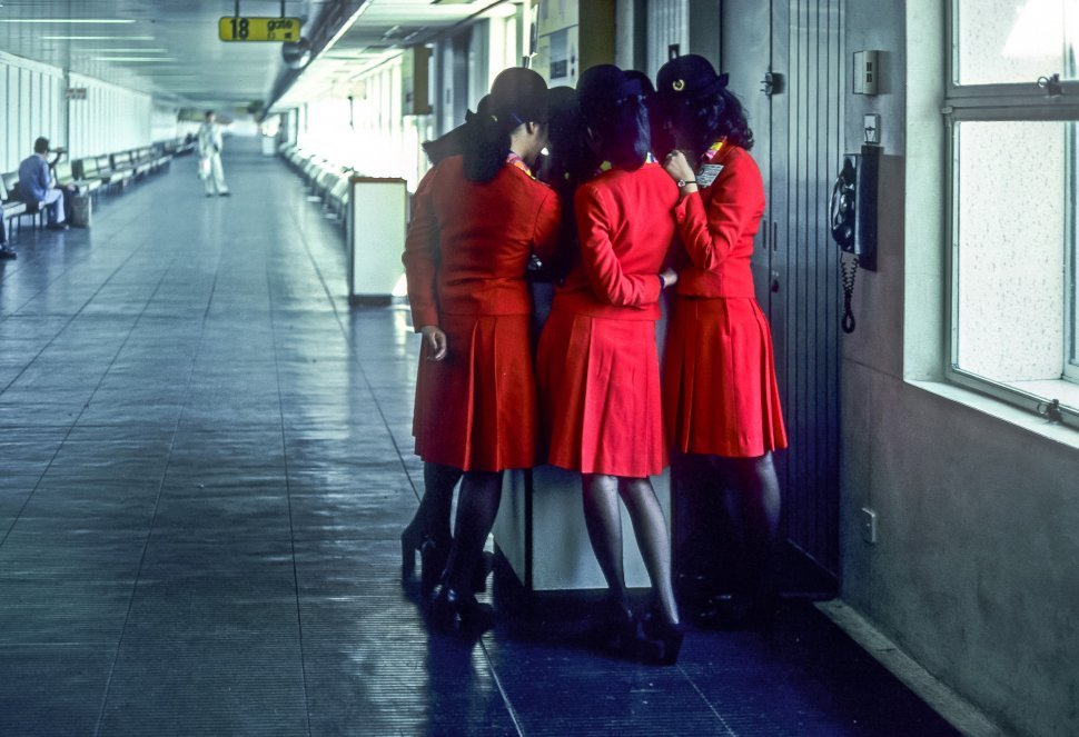Free image of Group of flight attendants speaking to eachother in an airport concourse.