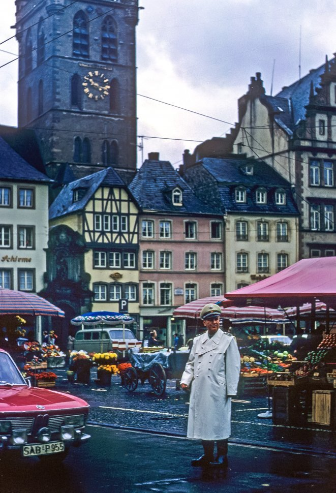Free image of Crossing guard directing traffic with a city square behind him, Germany