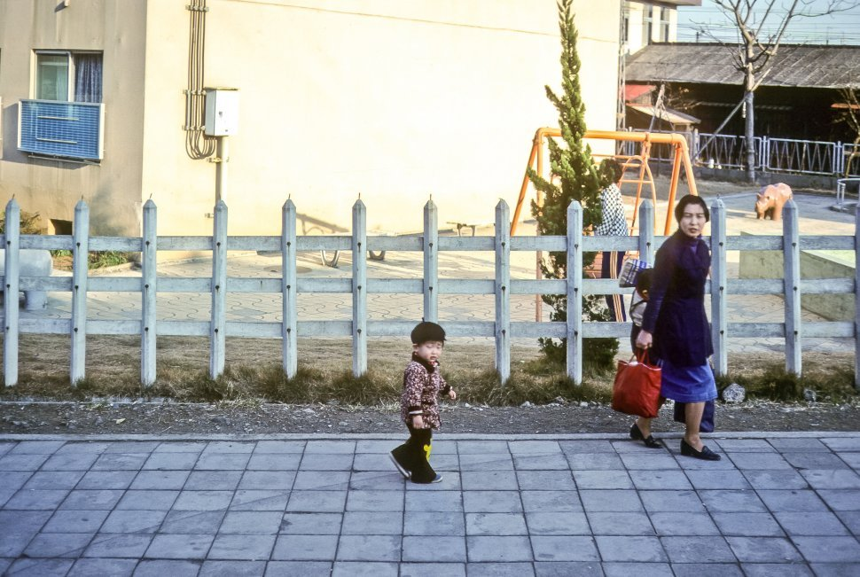 Free image of Mother and children walking past a schoold yard, Asia