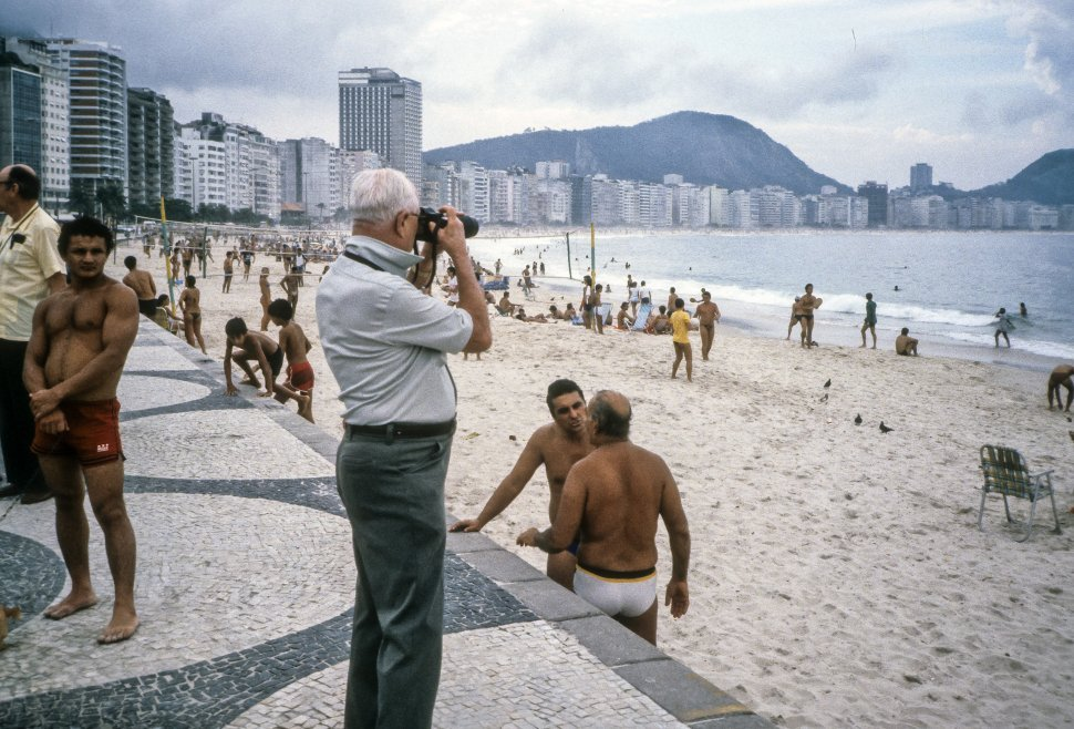 Free image of Tourist photographing a large group of tourists enjoying the beach in Rio de Janeiro, Brazil