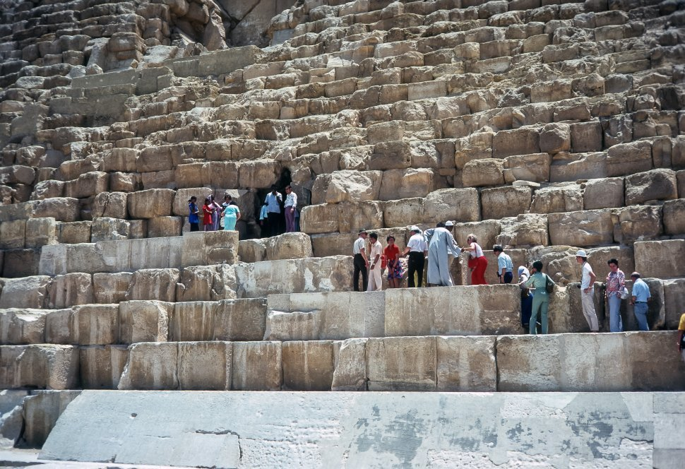 Free image of Large group of tourists climbing the large stones of the Great Pyramid, Egypt