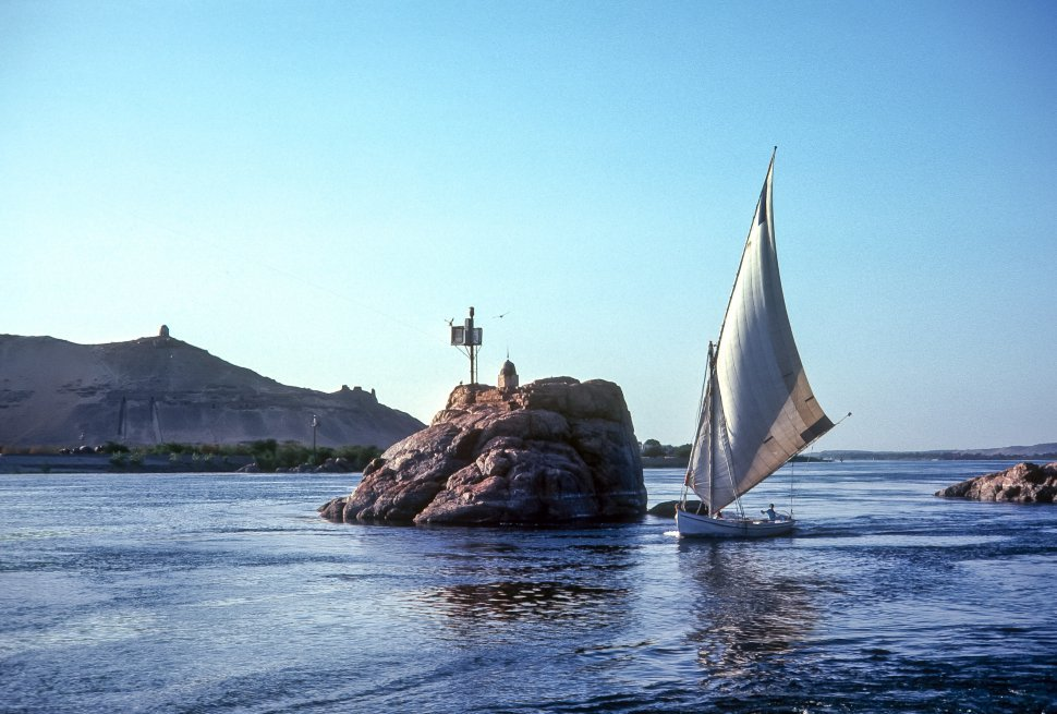 Free image of Sailboat passing by a large boulder in the water