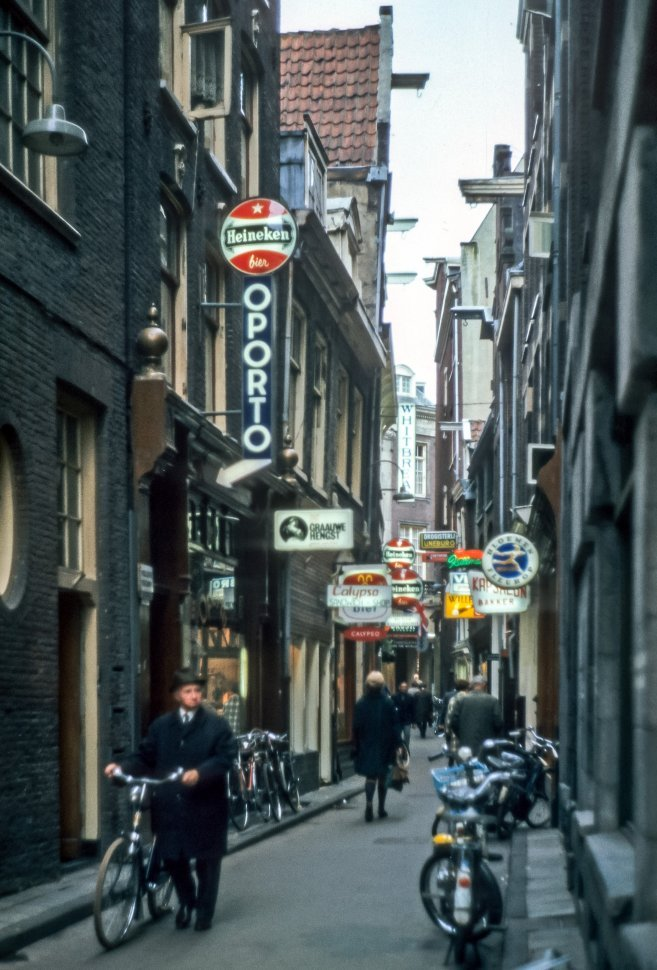 Free image of Man walking a bicycle down a small alley filled with bars and lighted signs, Europe