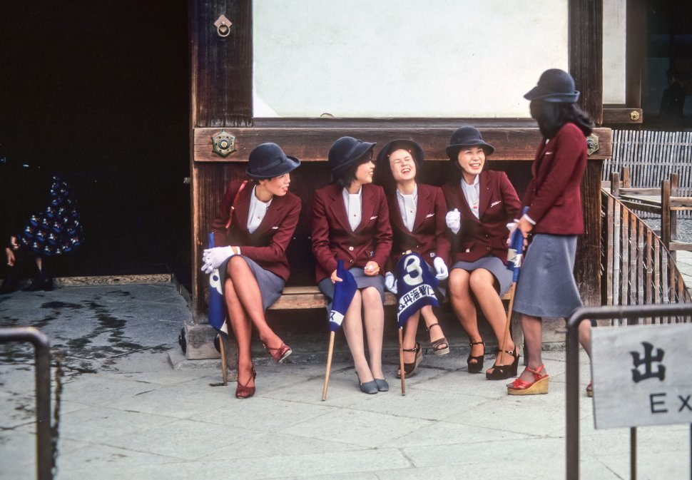 Free image of Group of female tour guides laughing together on a bench, Asia