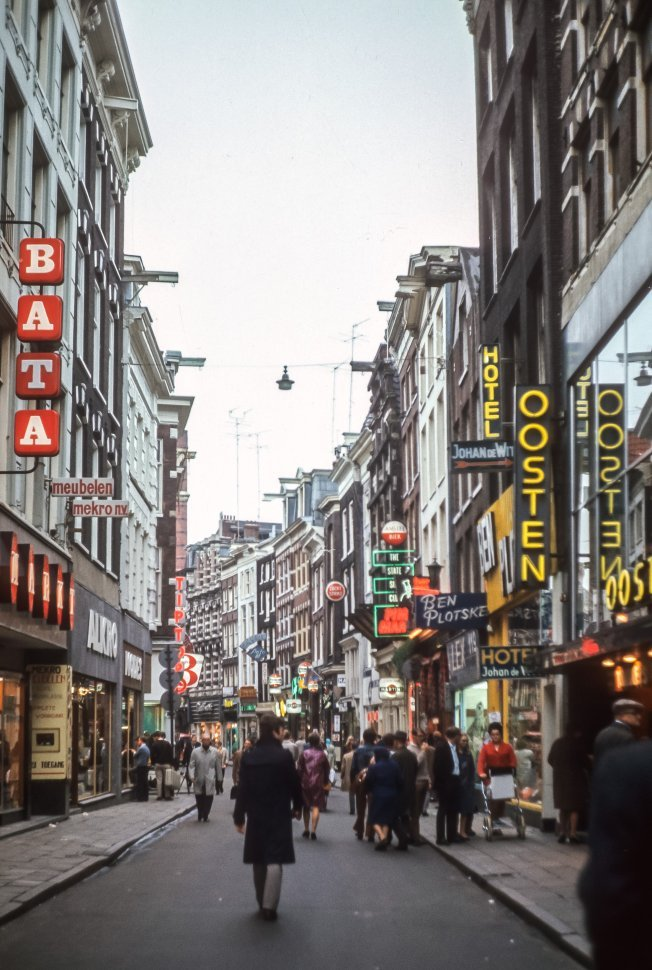 Free image of Small narrow street with brightly lit signs and people walking about, Germany