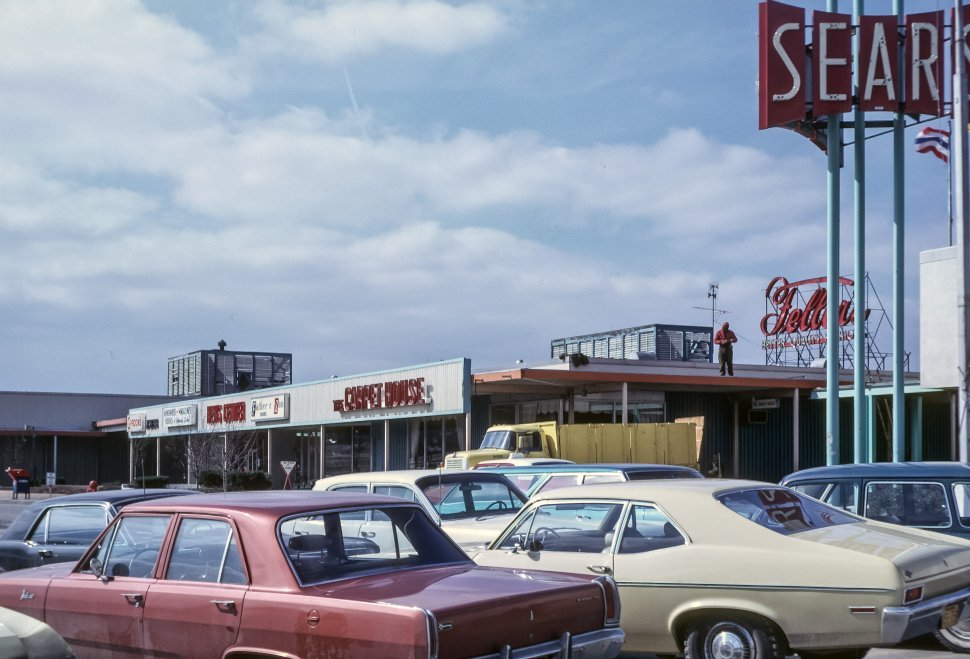 Free image of Image of a man on top of Sears above the parking lot full of vintage cars, USA