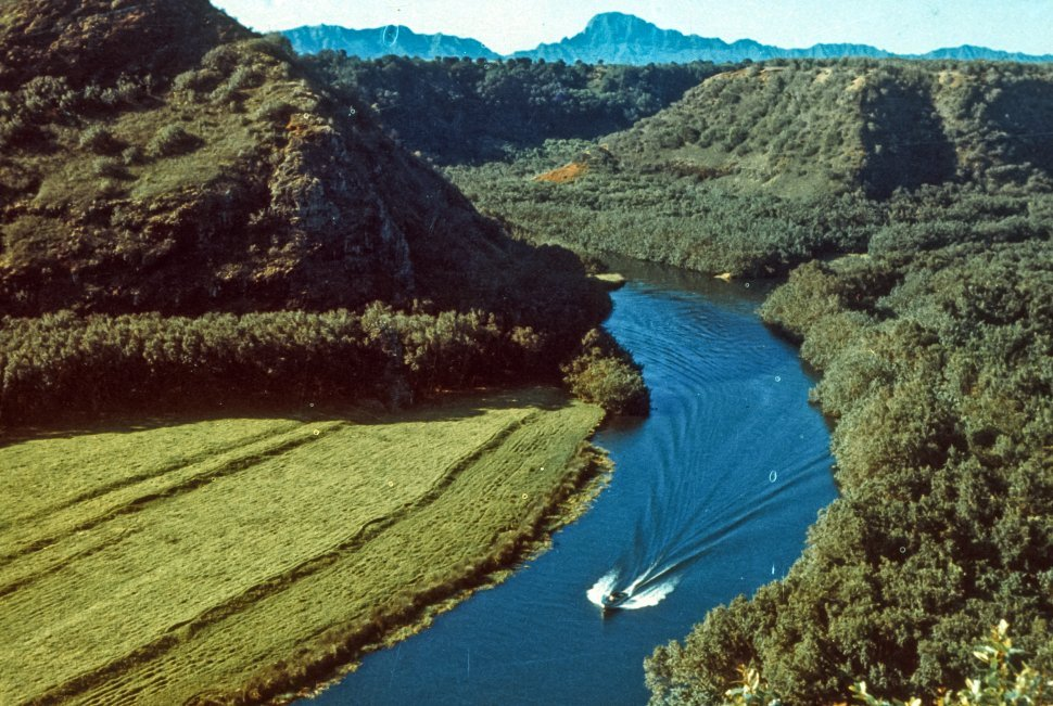 Free image of Small boat moving up a small river between lush hills.