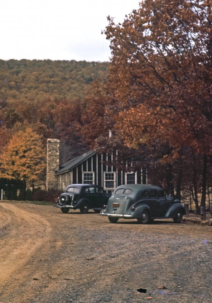 Free image of Two vintage cars parked outside a cabin, USA