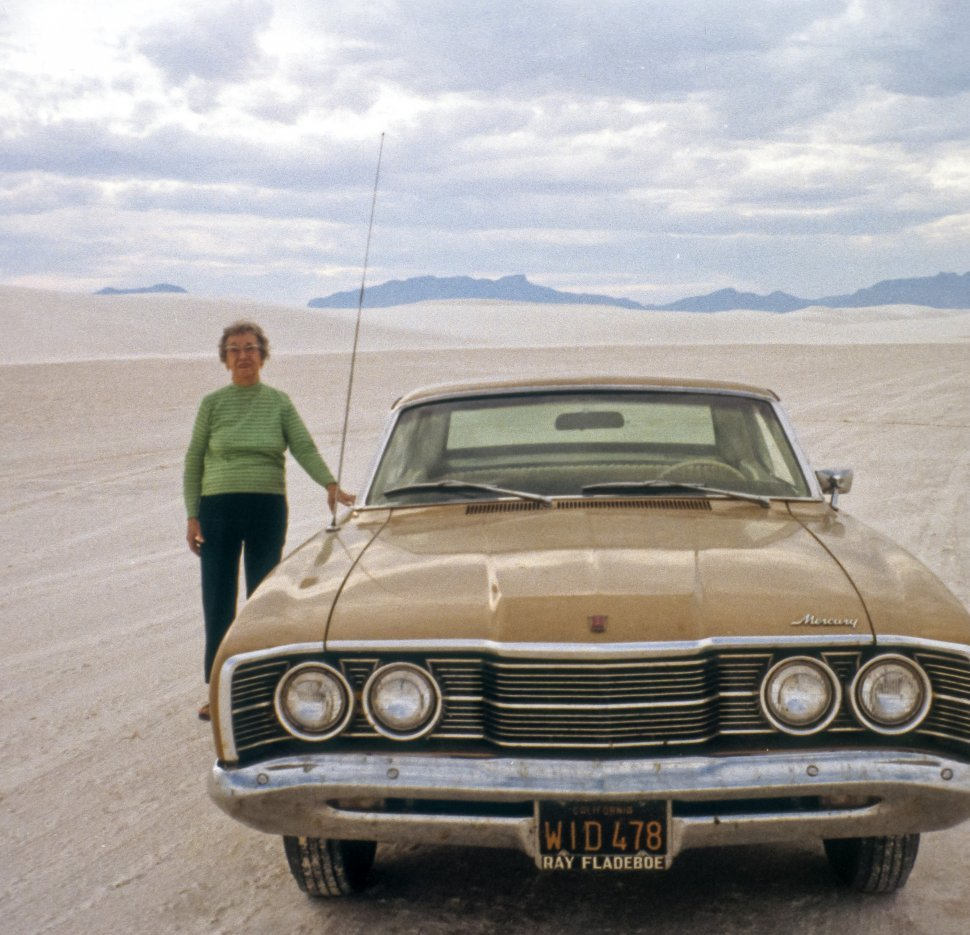 Free image of Woman posing with a vintage car at Great Sand Dunes National Park, Mosca, Colorado, USA