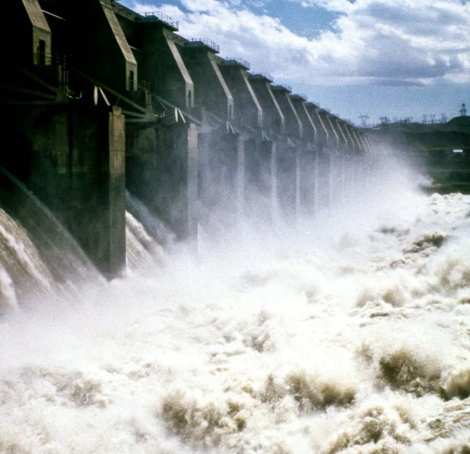 Free image of Water rushing through a large cement dam.