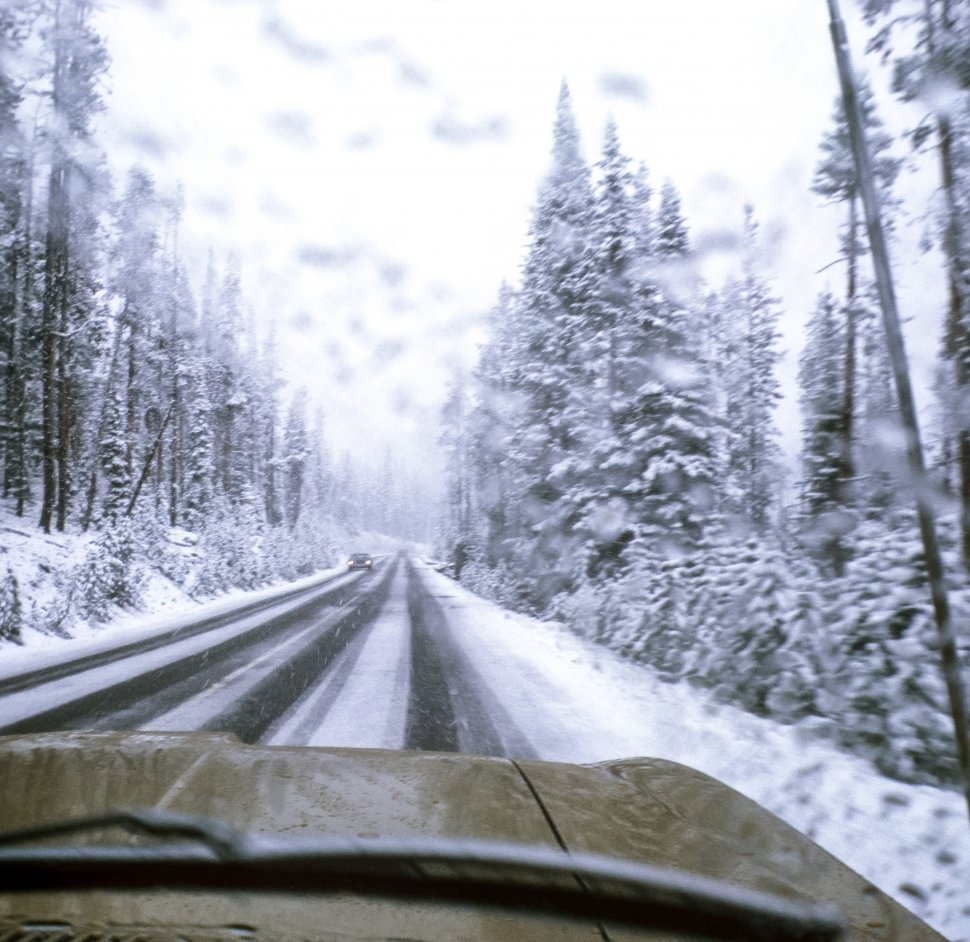 Free image of View from the inside of a car on a snowy road and forest, USA