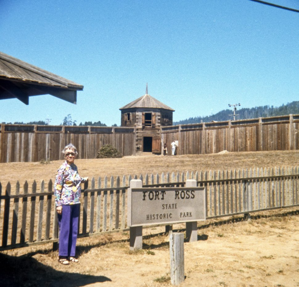 Free image of Woman posing next to the sign for Fort Ross, California, USA