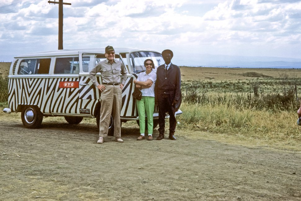 Free image of Three people standing in front of a zebra painted Volkswagen van, Africa