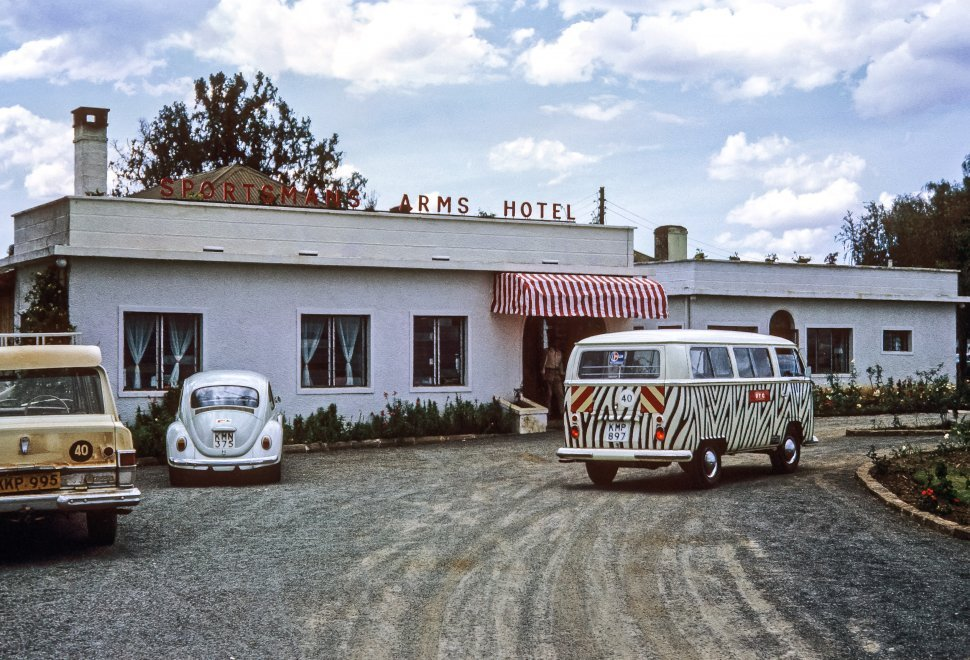 Free image of Zebra painted Volkswagen tour bus parked in front of the Arms Hotel, Kenya, Africa