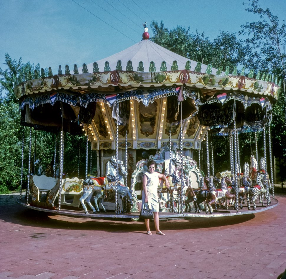 Free image of Woman posing in front of a merry go round or carousel, USA