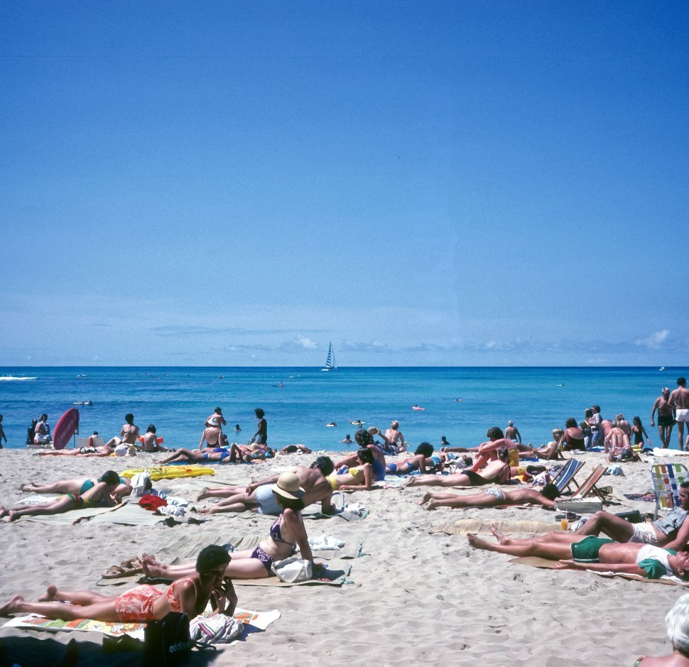 Free image of Large group of tourists sunbathing on the beach.