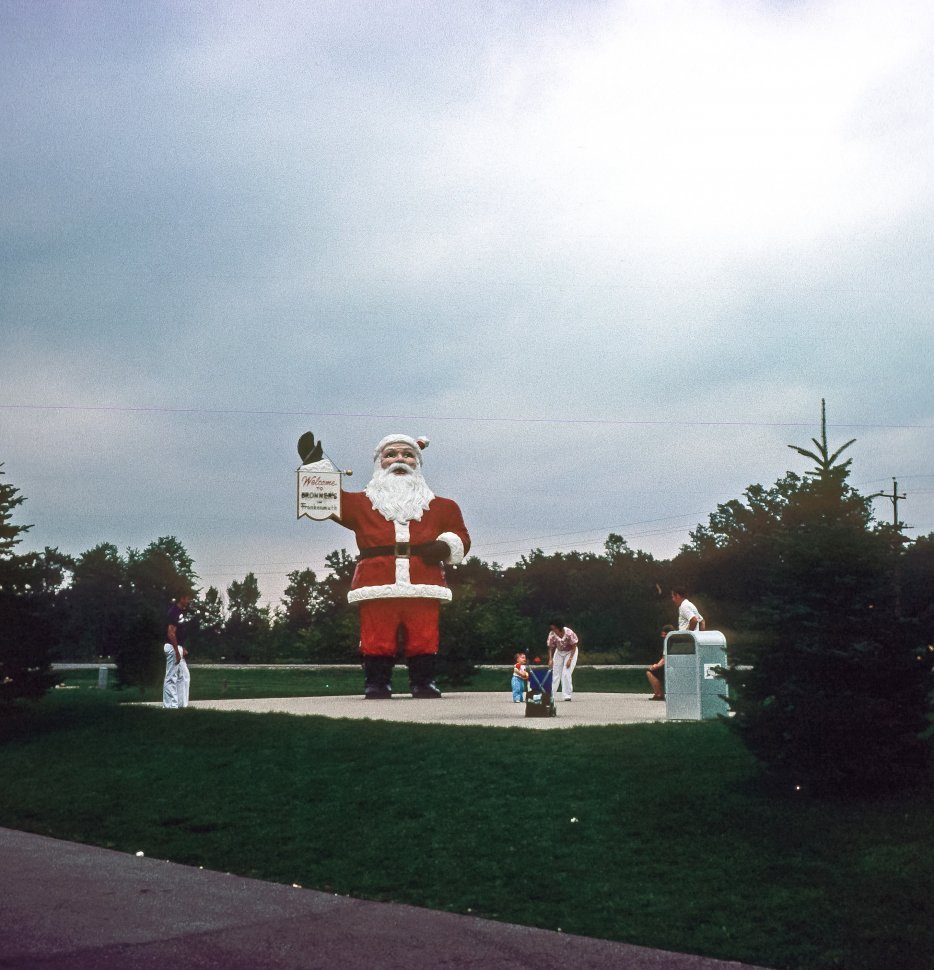 Free image of Family playing in front of a Santa Claus Statue at Bronner s Christmas Wonderland, Michigan, USA