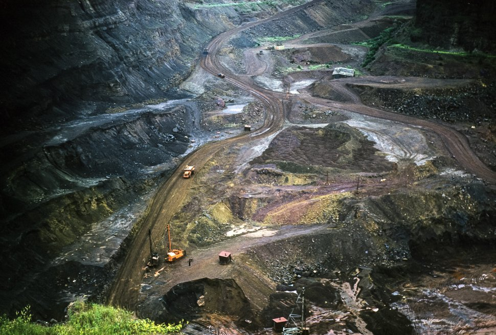 Free image of Erosion and land stripping caused by mining with trucks driving below.