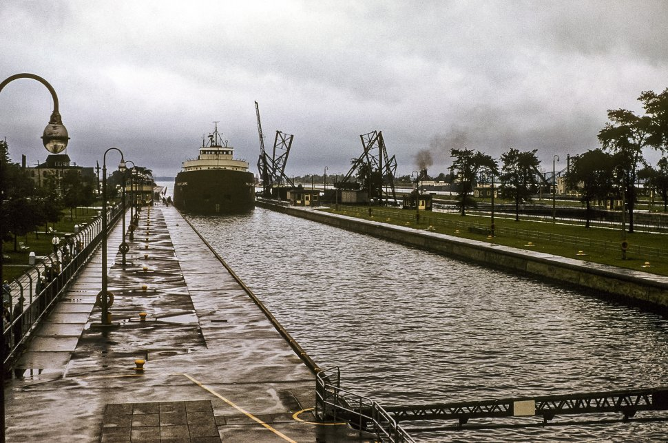 Free image of Ship moving up a canal on a cloudy day.