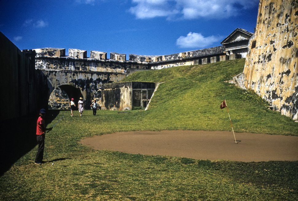Free image of Four tourists golfing through an ancient stone castle.