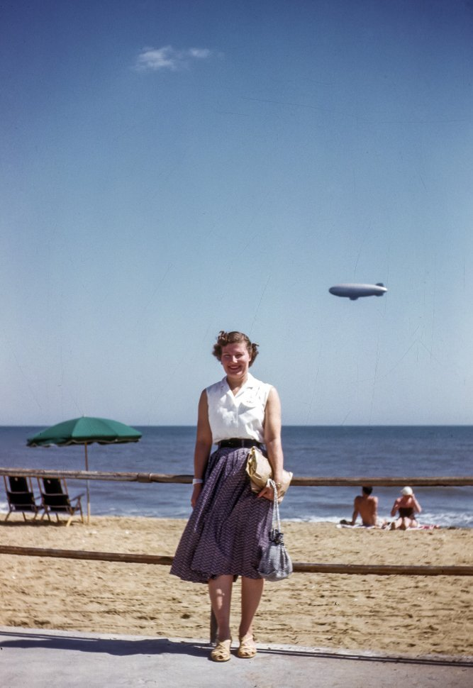Free image of Woman posing for a photograph on the boardwalk with a blimp and beach goers in the background, USA