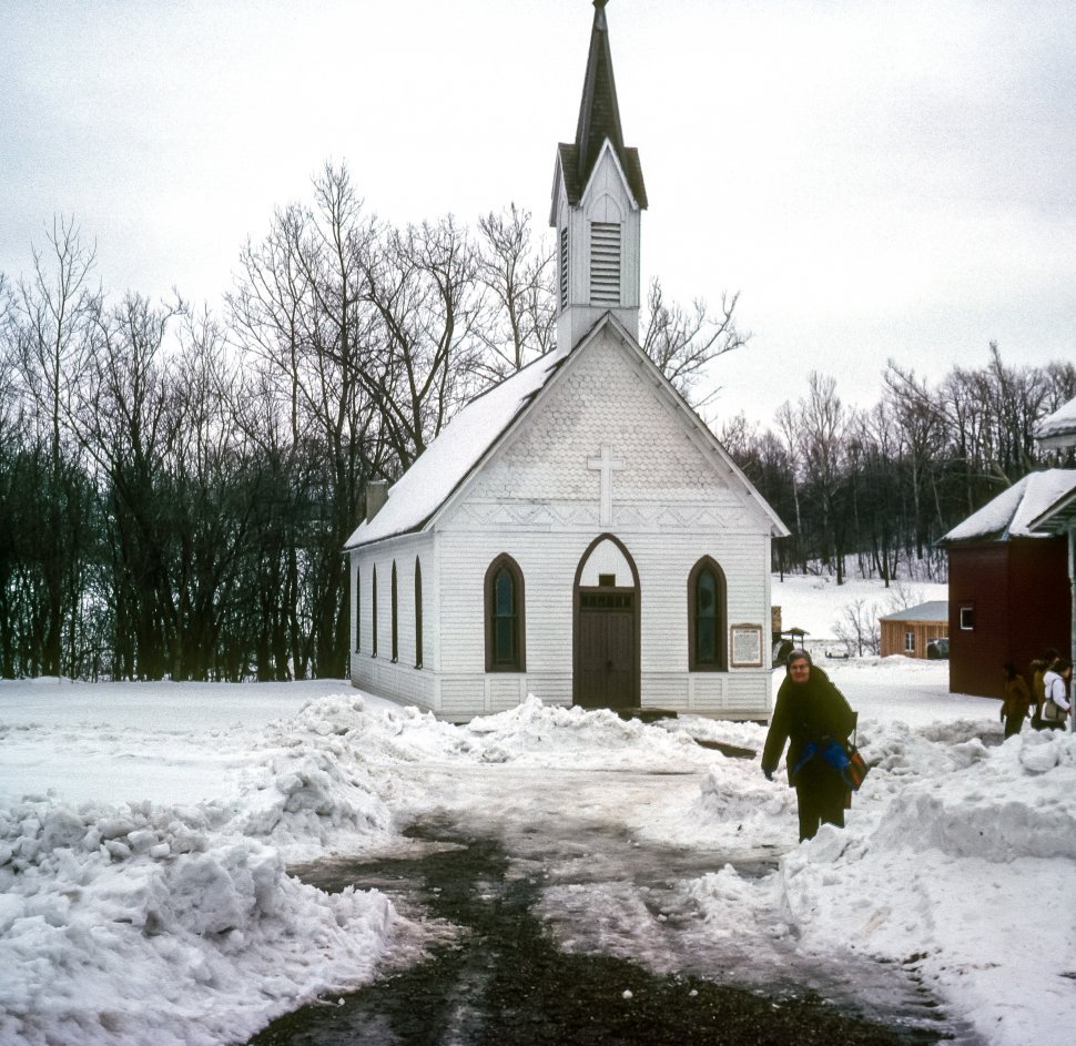 Free image of Woman walking through a snowy parking lot in front of a small white church, USA