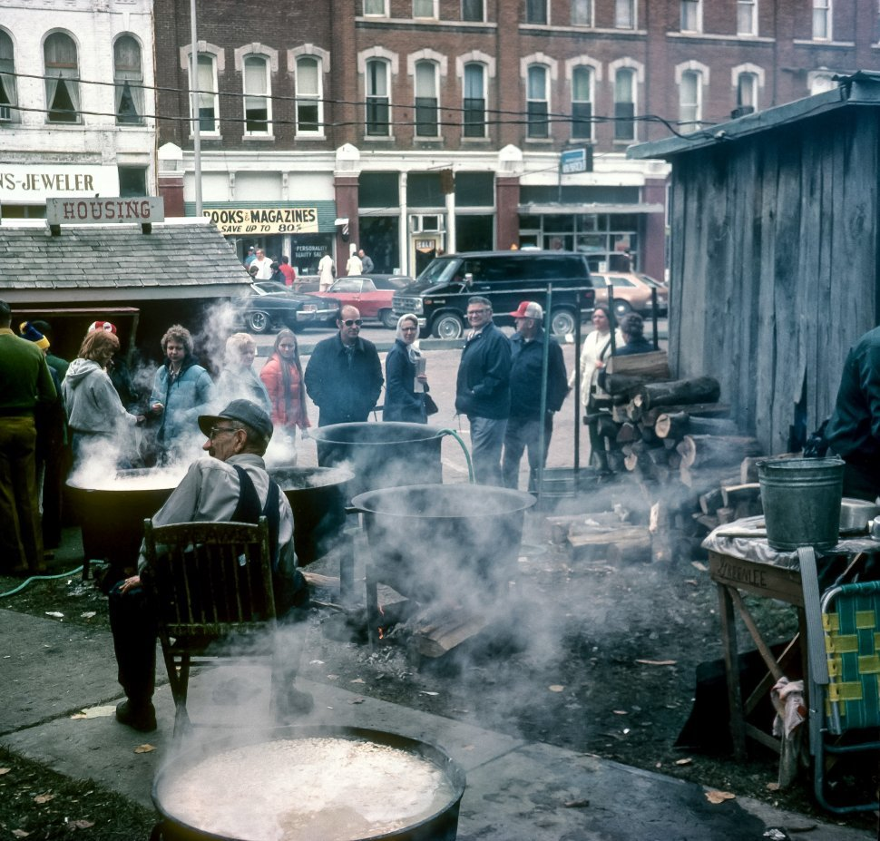 Free image of Group of people watching a man boil water in a historical re-creation, USA