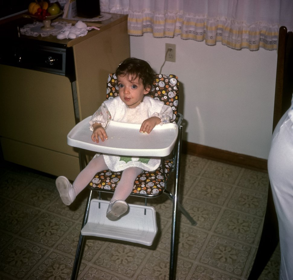 Free image of Little girl smiling for a picture in her high chair, USA