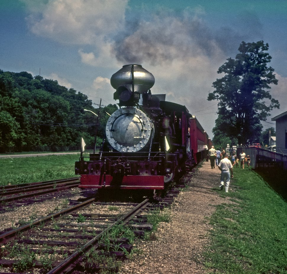 Free image of Train engine sitting on the tracks while tourists get off the cars, USA