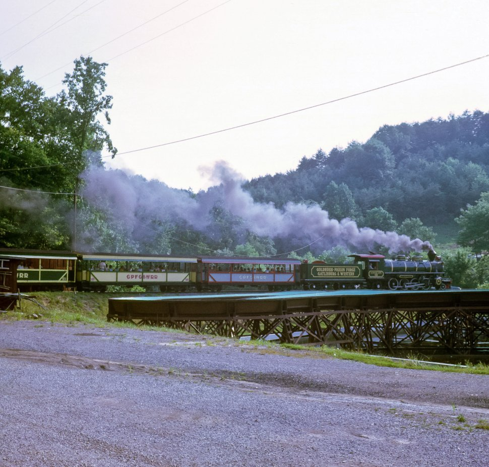 Free image of Train tour crossing a bridge with tourists riding in open cars behind,, Tennessee USA