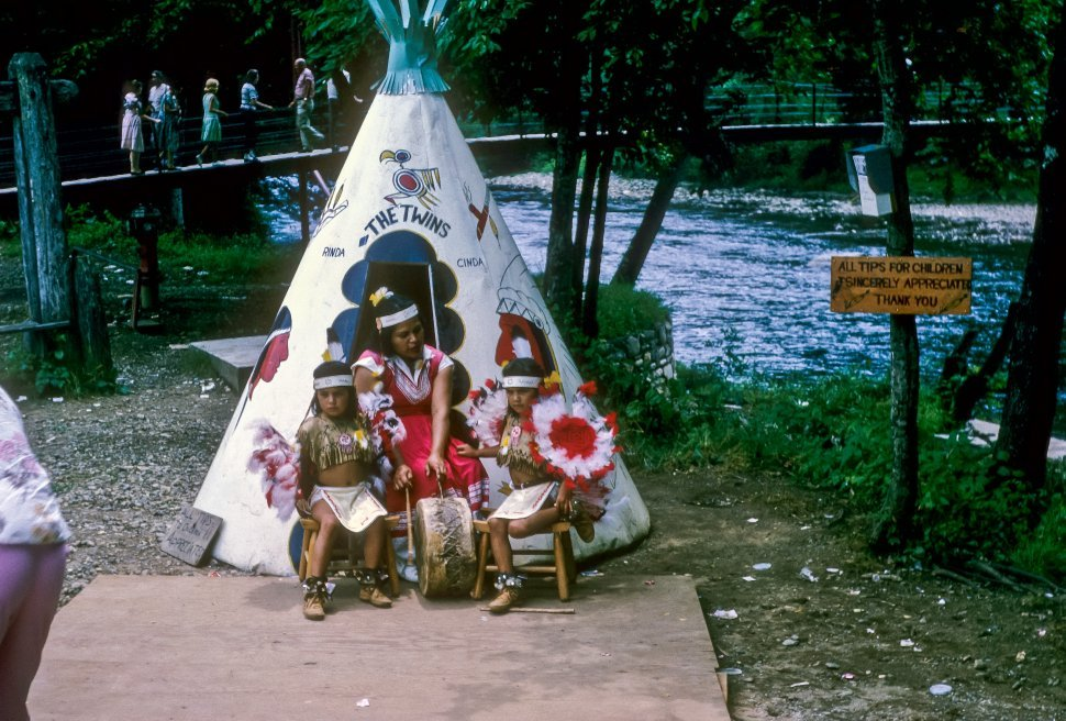 Free image of Woman and two young girls performing as Native Americans with tourists walking around, USA