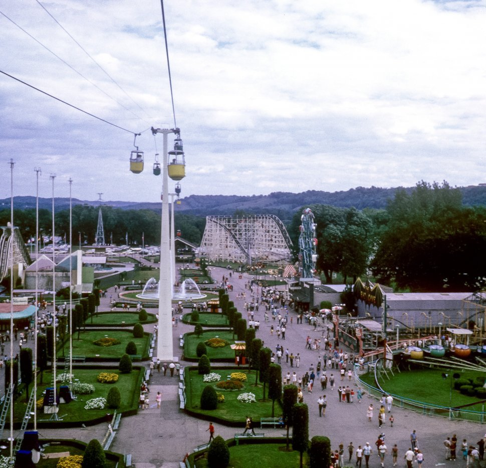 Free image of Tourists riding a tram above an amusment park.