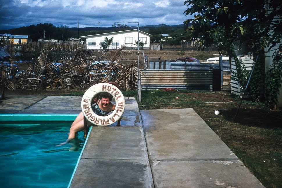 Free image of Humorous picture of a woman looking through a lifesaver beside a swimming pool. Hotel Villa Parguera, Puerto Rico