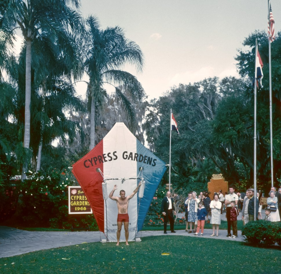 Free image of Man performing with a giant kite in front of a crowd of tourists at Cypress Gardens theme park, Florida, USA