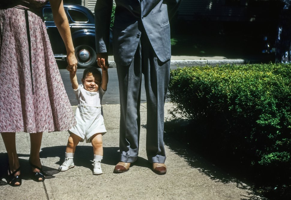 Free image of Parents holding the hands of their baby attempting to walk, USA