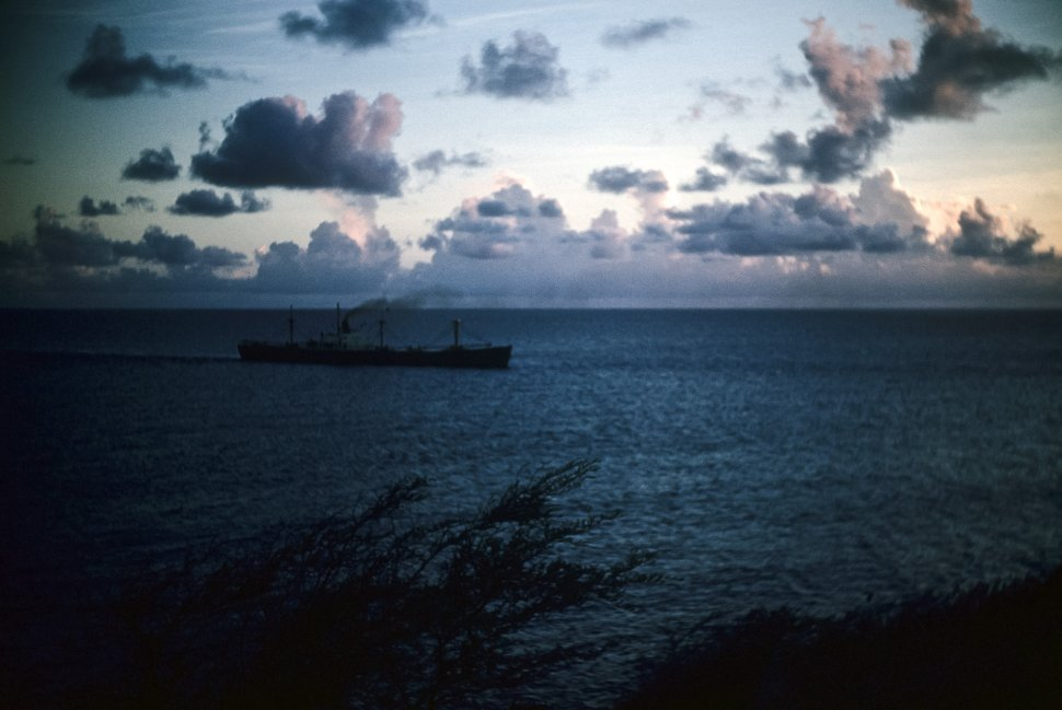 Free image of Ship passing by in the darkening night with smoke trailing.