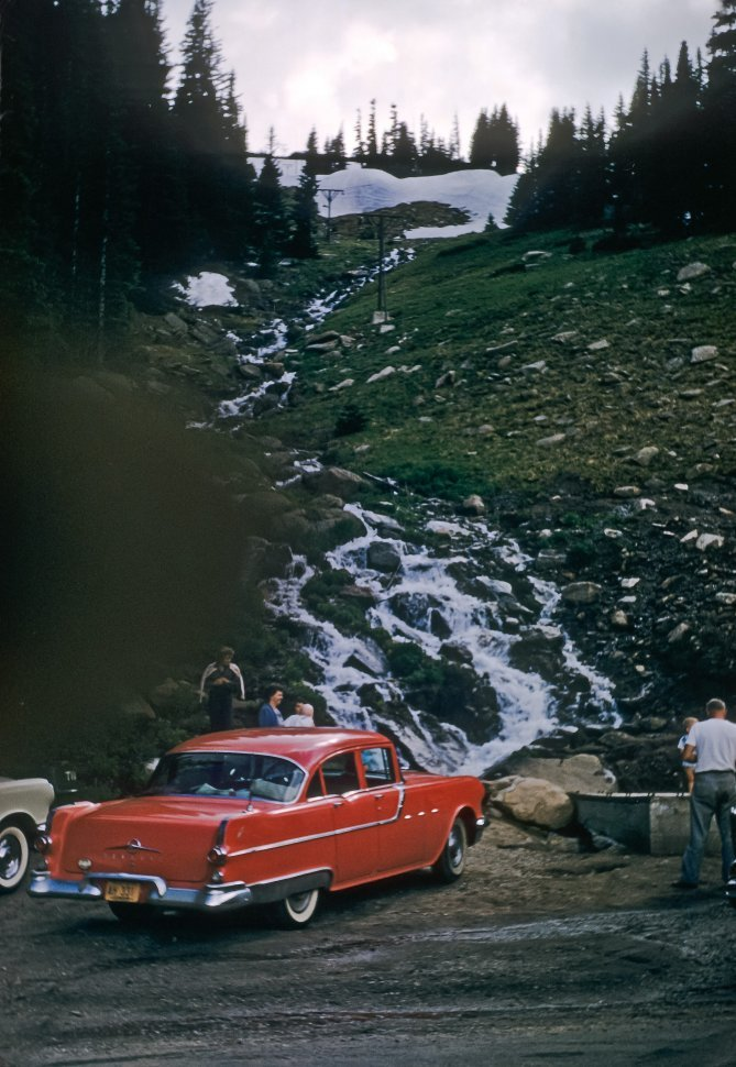 Free image of Tourists visiting a stream flowing down the side of a small hill by a rest stop.