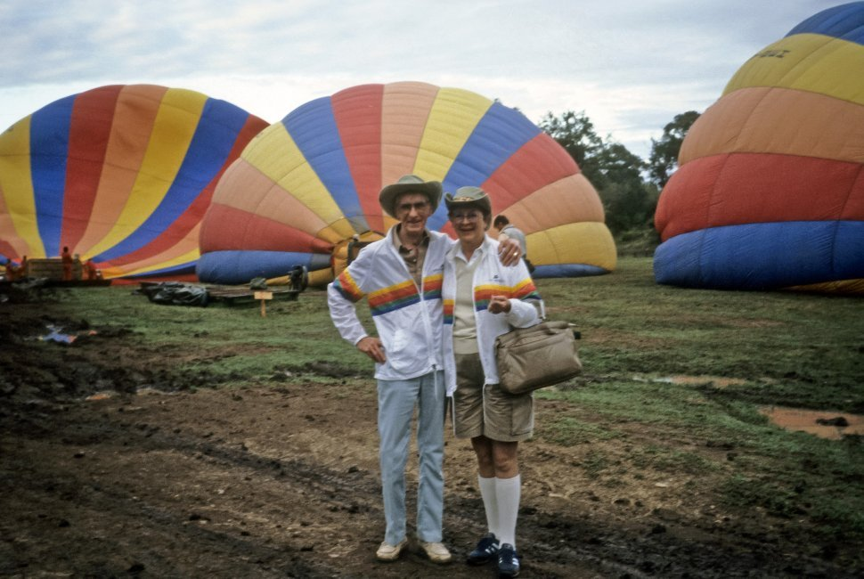 Free image of Two tourists posing on front of hot air balloons filling before their flight.