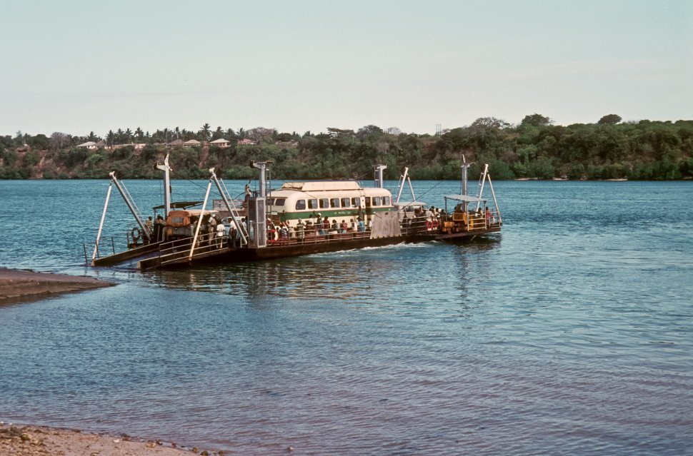 Free image of Tour bus being carried across a river by a ferry crowded with tourists.