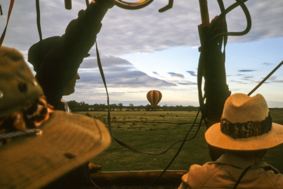 Free image of Tourists watching another balloon start to take off in the distance.
