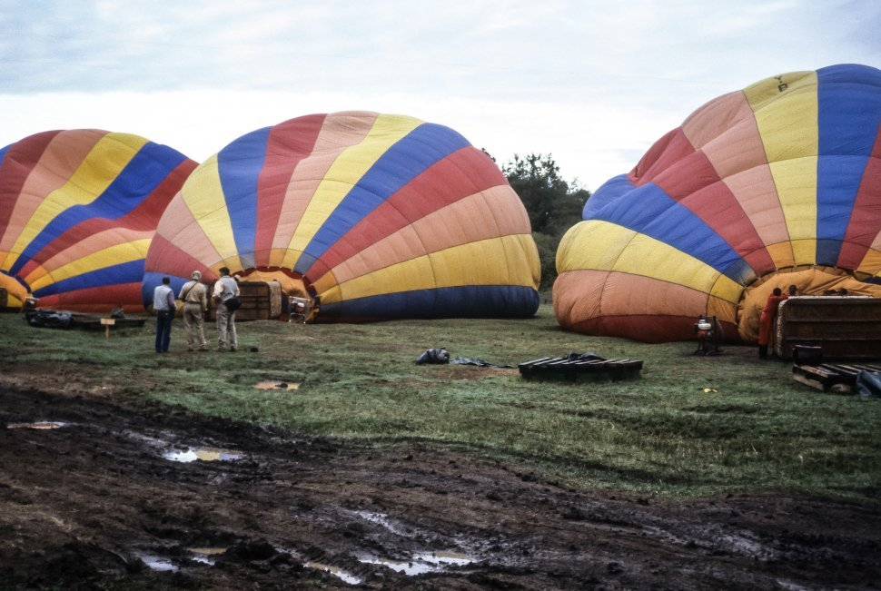 Free image of Three tourists standing and watching a hot air balloon being filled.