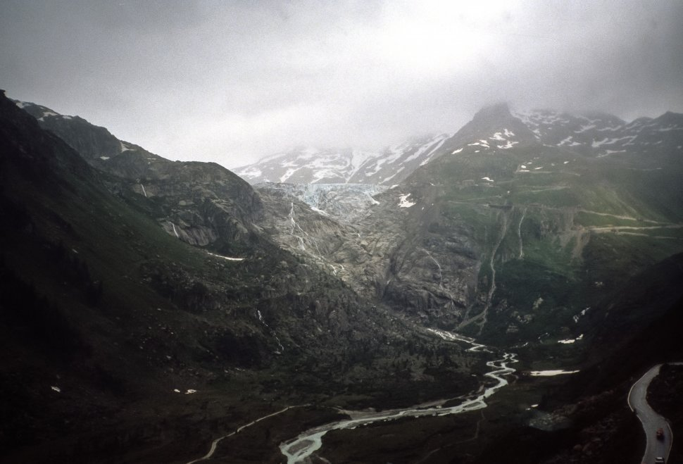 Free image of Storm forming above a mountain valley with a river running through it, Europe