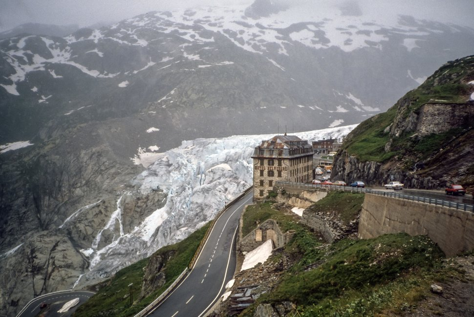 Free image of Furka Pass, Switzerland, Mountain hotel sitting precariously on a cliff with a winding road around it, Europe