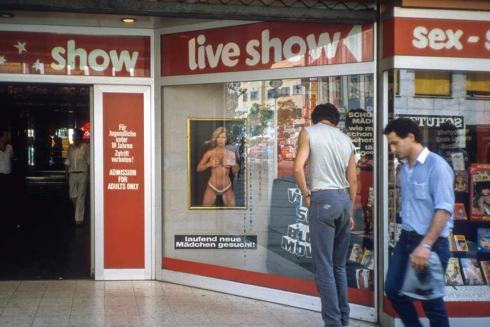 Free image of Man browsing the shop windows of a sex shop.