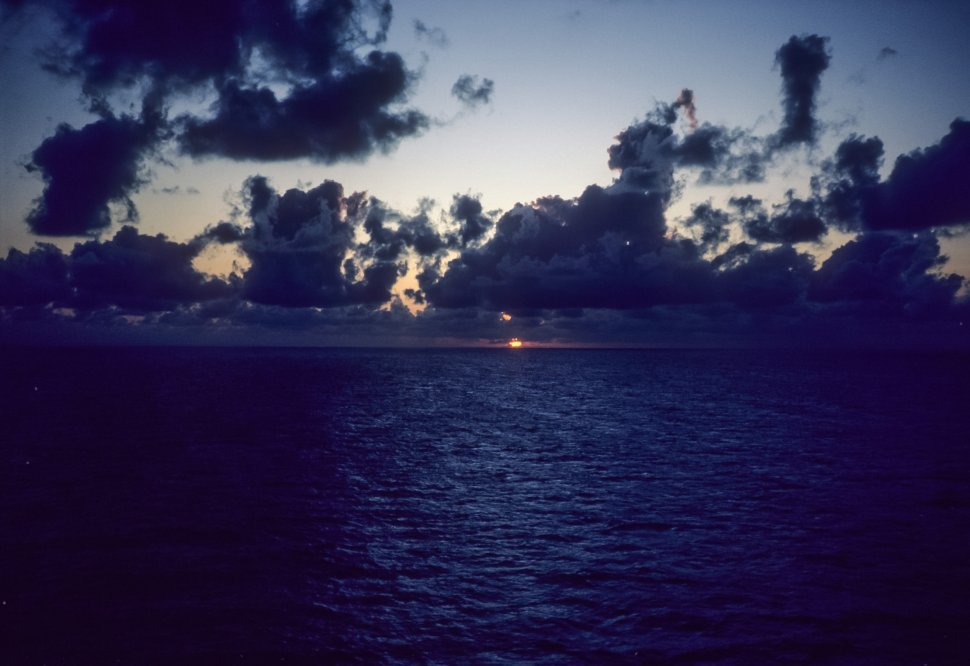 Free image of Darkening sky with sun setting below the ocean.
