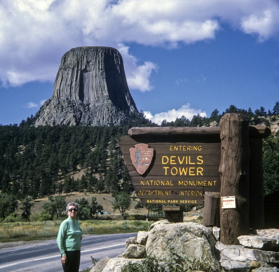 Free image of Woman posing next to a sign at the entrance to Devil s Tower National Monument, Wyoming, USA