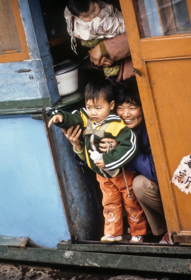 Free image of Mother and child waving from a doorway at the camera, China