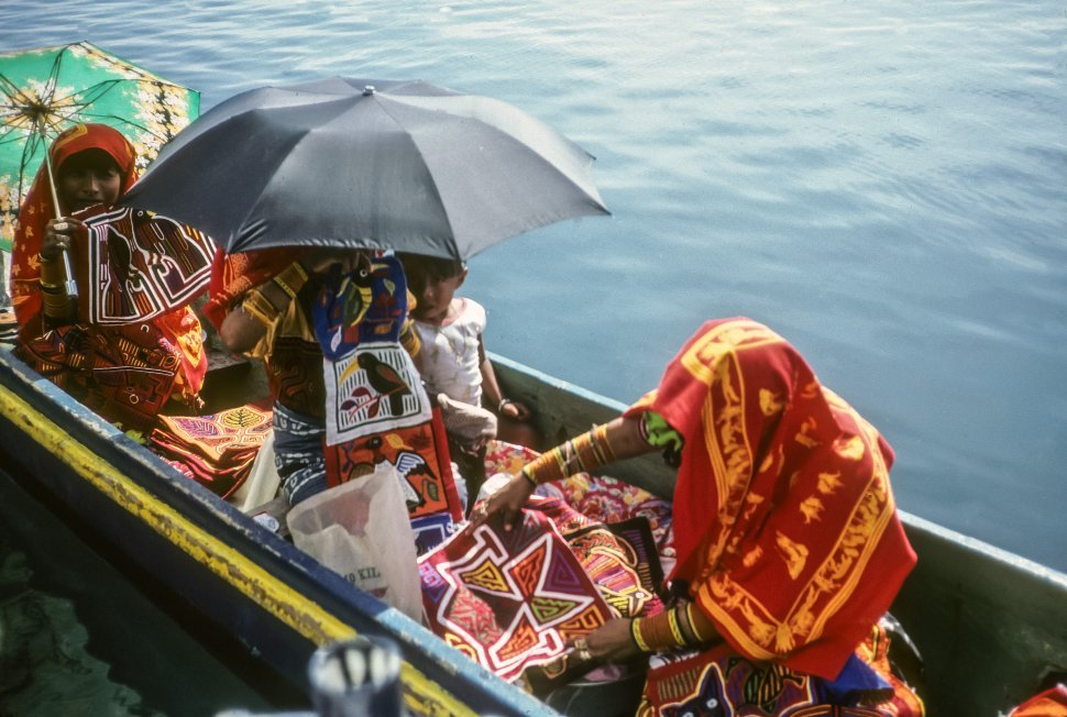 Free image of Women selling textiles from a small boat to tourists, Ecuador