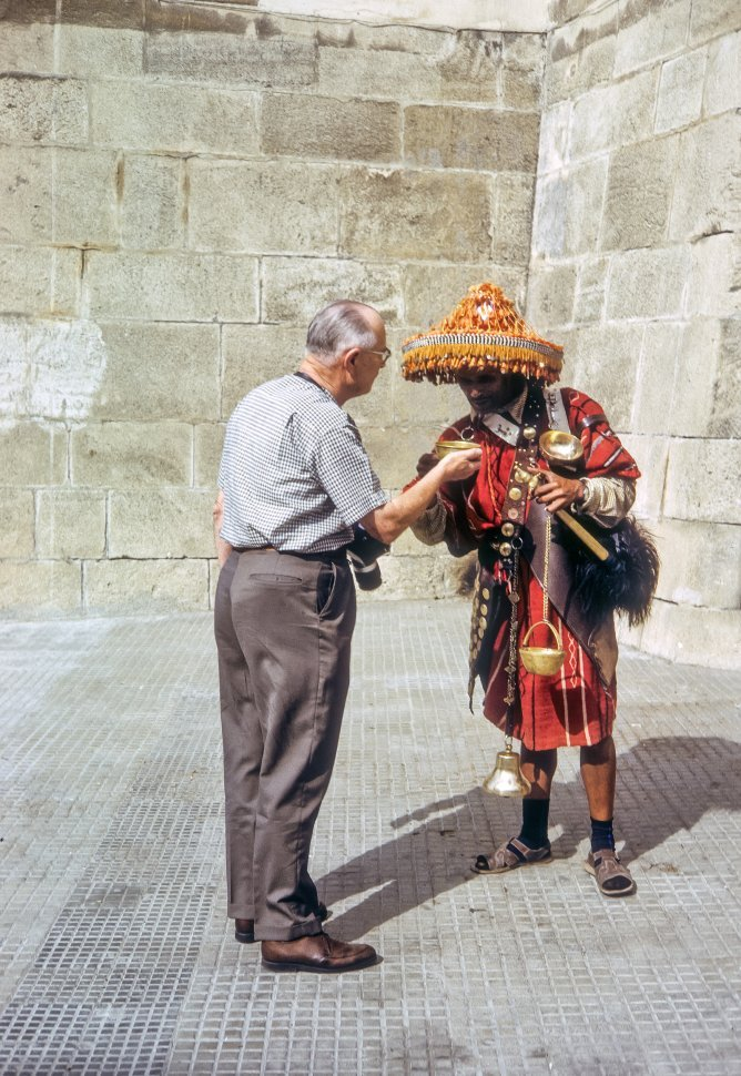 Free image of Tourist conversing with a local in traditional garb as he offers him a gold bowl, Africa